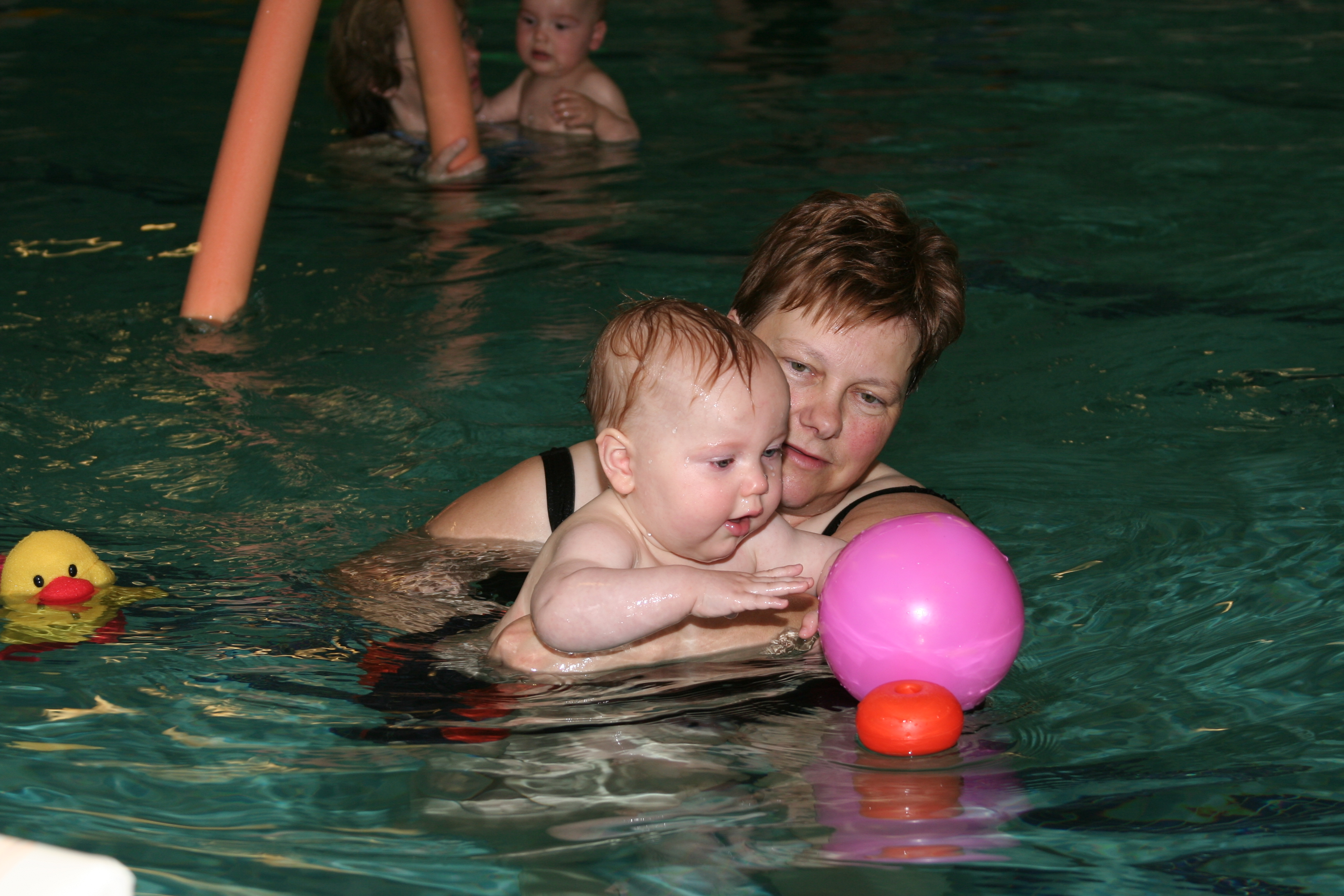 Kind watergewenning met bal in het water